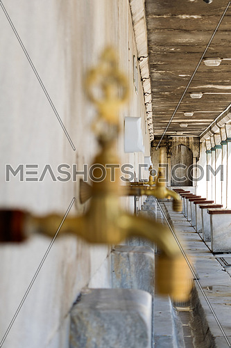 A closeup of a golden water on a wall with other water taps on the background
