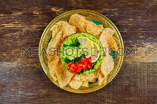 Fresh green guacamole with lime juice and nachos and on wood background
