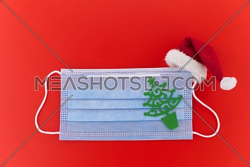 Face mask with paper cut Christmas tree and and Santa hat over a red background with copyspace