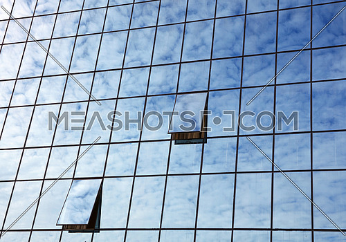 Cloudy blue sky reflection in glass of office business building with open windows, low angle view