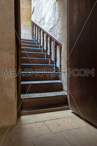 Open wooden door revealing wooden old staircase going up located at the House of Egyptian Architecture historical building, Cairo, Egypt
