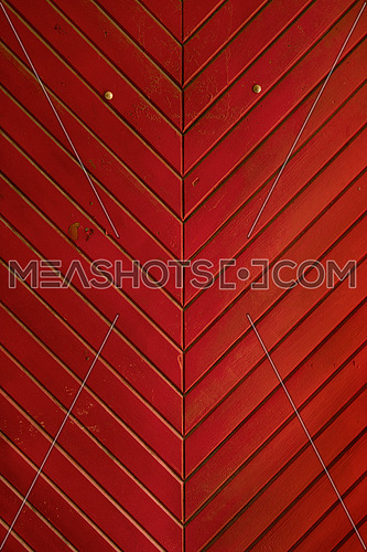 Red vintage grunge stained aged painted wooden panel medieval style door with diagonal planks