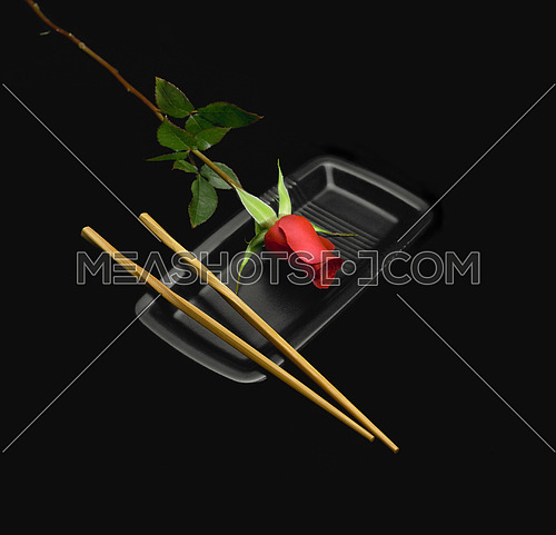 red rose on a japanese plate with chopstick over black background