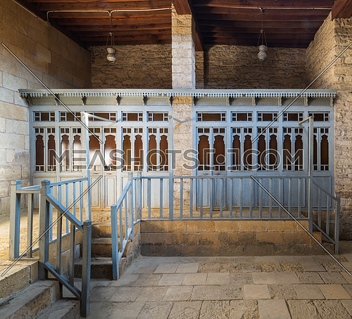 Changing rooms with blue wooden door shutters and wooden balustrades at abandoned historical traditional Turkish public bathhouse, Moez Street, Cairo