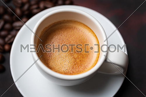 White cup of coffee and coffee bean on dark background. Copy space.close up view.