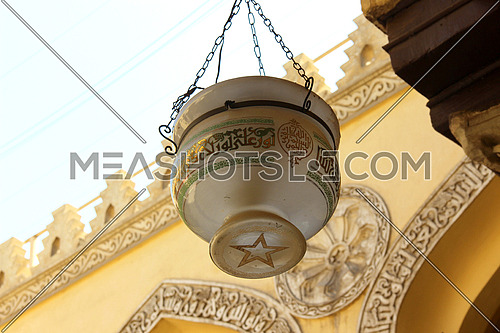 a photo for Al Aqmar mosque in old Islamic Cairo , Egypt showing the traditional lamps used for lighting at that times