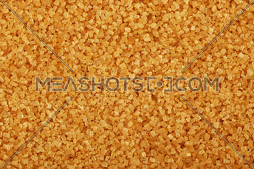 Close up background texture of brown raw cane sugar, elevated top view, directly above