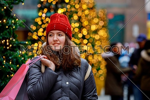Close up fashion lifestyle portrait young girl, with shopping bags walking out from shop in the street, colorful lights bokeh background
