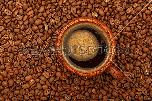 Brown coconut palm carved wood cup full of black coffee with froth on background of roasted coffee beans, elevated top view, directly above