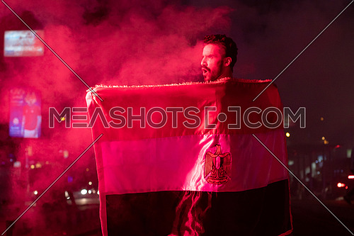 Egyptian football supporters in the street with Egyptian flag dressed in red