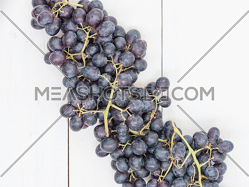 Purple grapes on white wooden table with copyspace. Flat lay or top view