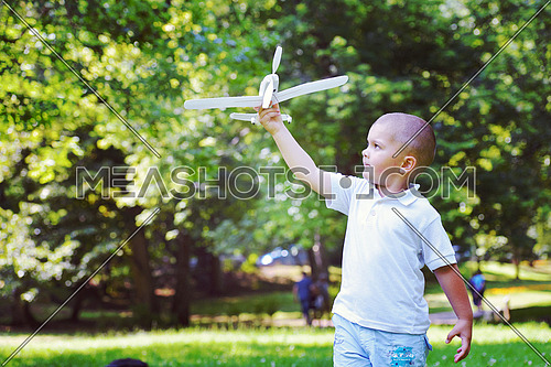happy boy play and  throw airplane in park