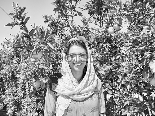 Young beautiful middle eastern woman enjoys the farm orange with a smile on her face and orange in hands