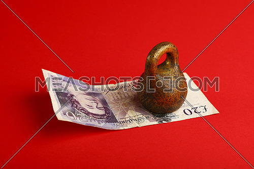 Close up one twenty British pounds paper currency banknote under pressure of heavy vintage metal weight over red background with copy space, high angle view