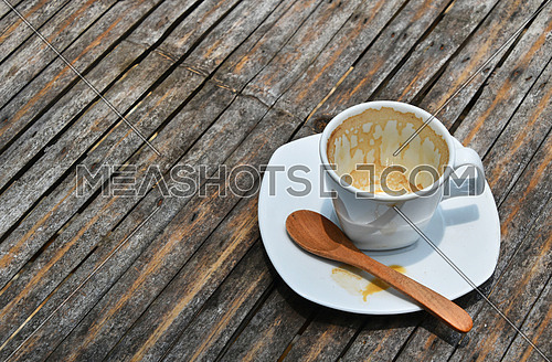 One overdrunk finished white cup of espresso coffee on porcelain saucer with wooden spoon on old vintage bamboo table