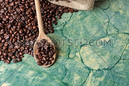 Coffee beans in coffee burlap bag on green surface and wooden spoon with coffee beans on top.