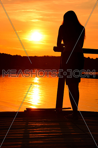 Dark silhouette of one young woman standing on wooden pier over vivid orange sunset sky and lake water background, rear view