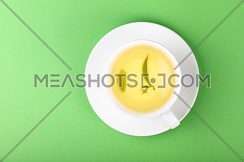 Close up one full white cup of green oolong or herbal tea on saucer over pastel green paper background, elevated top view, directly above