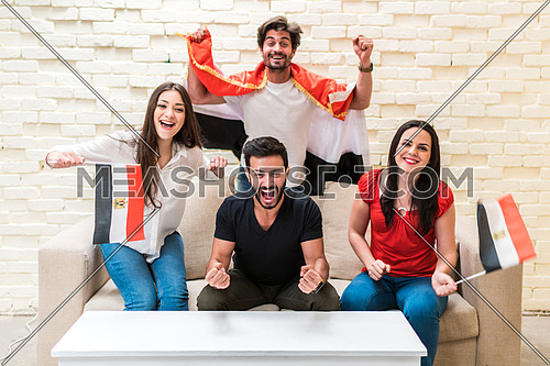 group of young people sitting on a sofa cheering for a football match in front of white table holding egyptian flags