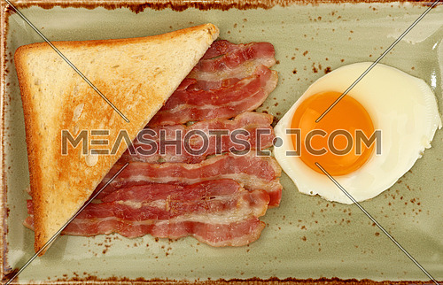 Close up English breakfast, sunny side egg, half of toasted bread and roasted bacon slices on blue plate, elevated top view, directly above