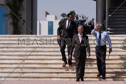 Group of business executives walking in front of a corporate building