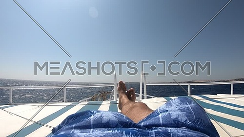 Long shot for the sea from boardside of boat showing male tourist legs relaxing at day