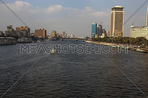 a photo from Cairo ,Egypt showing the other bank of the River Nile and boats , palm trees, and some buildings
