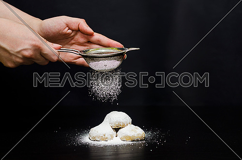 A woman sprinkling sugar from a strainer on top of Kahk and sugar is appears while sprinkling for Eid Fitr celebrations