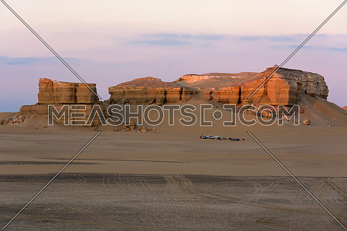 Desert landscape with camping tourism site under hill and mountains  in sunset light colors in Fayoum Wadi Nature Reserve , Egypt