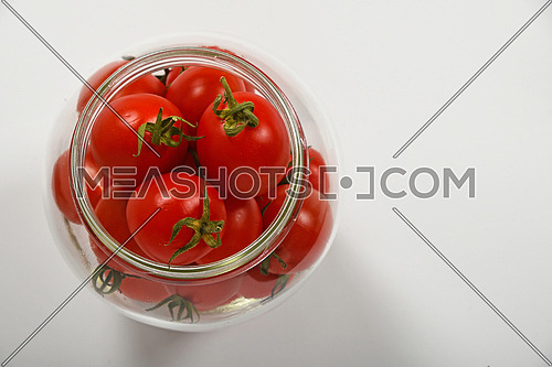 Glass jar full of red cherry tomatoes ready for conservation over white background, top view