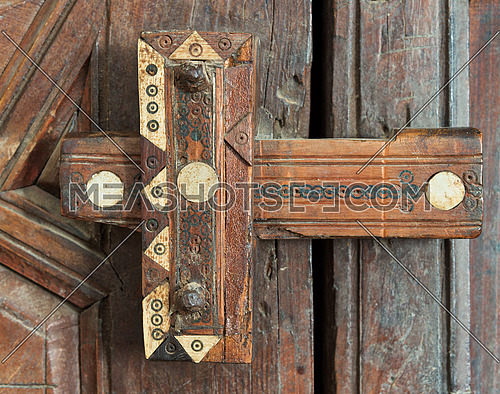 Closeup of a wooden aged ornate latch over a wooden door