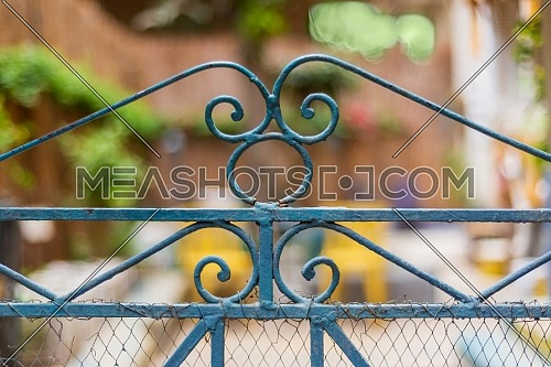 Vintage artistic green wrought iron gate with peeling paint and rust revealing blurred backyard garden in the background