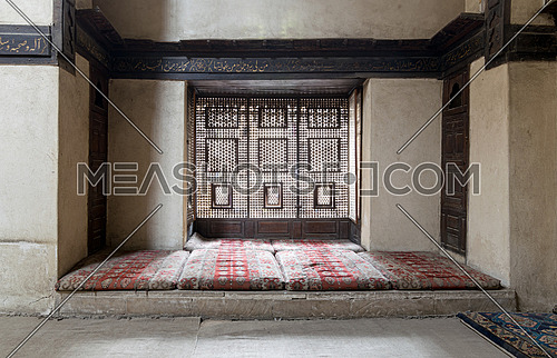 Interleaved wooden window (Mashrabiya) with built-in couch, and an embedded wooden cupboards at El Sehemy house, an old Ottoman era house in Cairo