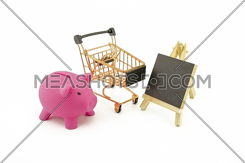 Pink pig saver, small chalk board and empty golden shopping cart isolated on a white background