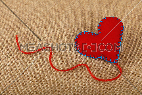 Valentine Day template, one handmade red felt craft stitched toy heart with jute twine on linen canvas, close up, high angle view