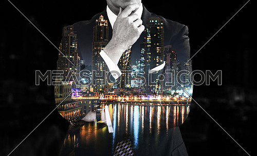 Night double exposure of senior businessman in front of the big city
