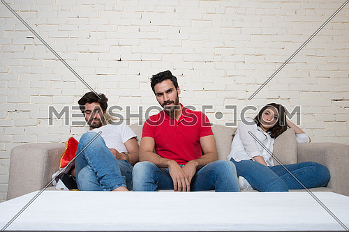 A group of bored middle eastern friends watching a football game in the living room