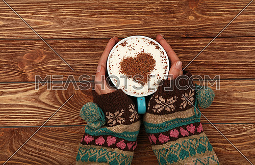 Close up two woman hands hold and hug big full cup of latte cappuccino coffee with heart shaped chocolate on milk froth over brown wooden table, elevated top view, directly above