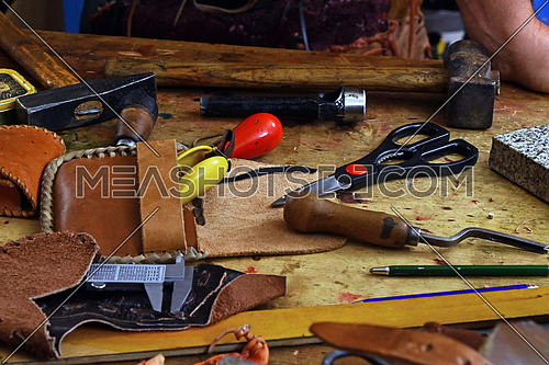 Working tools for leathercraft in wooden box on workbench desk, close up, high angle view