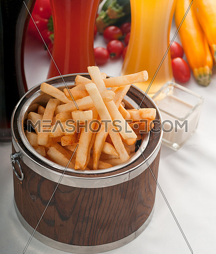 fresh french fries on a wood bucket with selection of beers and fresh vegetables on background