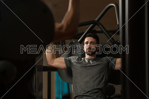 Young Muscular Fitness Bodybuilder Doing Heavy Weight Exercise For Shoulders On Machine In The Gym