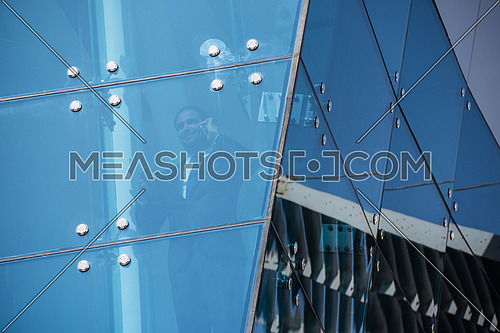 Outdoor shoot showing a young business executive talking over the phone through glass front of a corporate building with blue sky in background