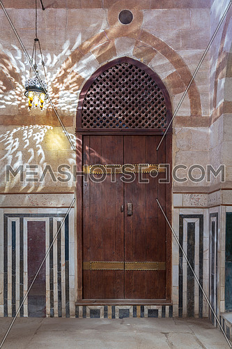 Wooden arched door on stone wall decorated with marble panels and lantern shadows on the wall, Khayer Bek Mausoleum, Darb Al-Ahmar district, Old Cairo, Egypt