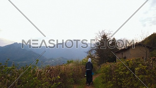Rear view of mother with stroller walking in a mountain path