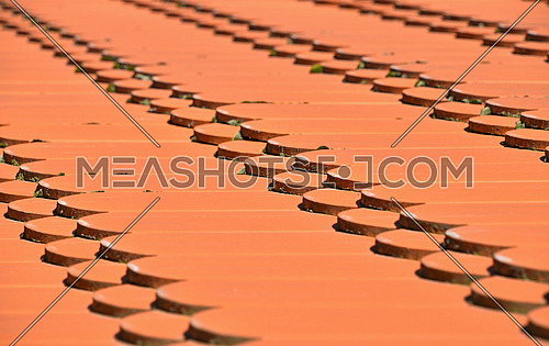 Traditional red brown ceramic roof tiles pattern background, close up, low angle diagonal view