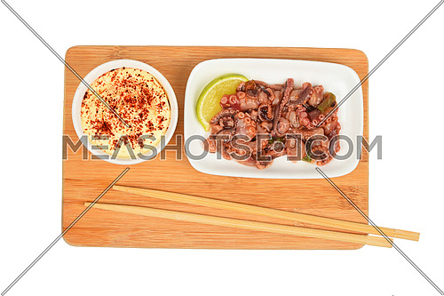 Portion of seafood octopus cuttlefish marinated salad in small white plate with sauce on bamboo wooden board with chopsticks isolated on white