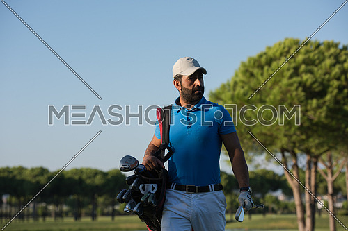handsome middle eastern golfer carrying  bag  and walking to next hole at golf  course