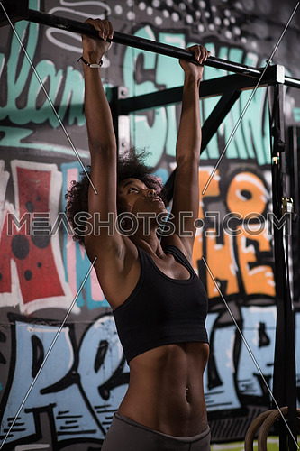 young beautiful african american woman athlete doing pull ups on the horizontal bar in the gym