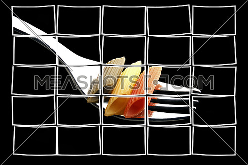 italian penne pasta on a fork on black background