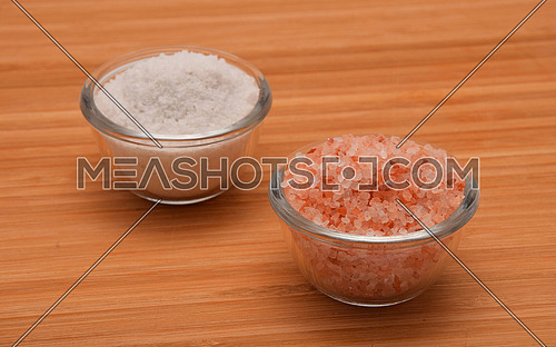 Choose your salt - Himalayan or rock salt (angle view) on wooden bamboo background